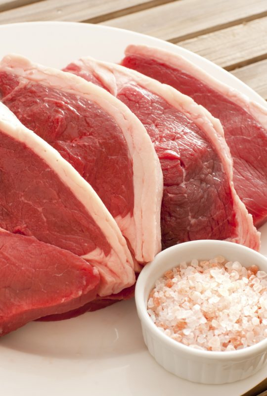 Four uncooked succulent beef steaks arranged ready for cooking on a plate with a bowl of rock salt and parsley garnish